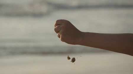 Female hand pouring sea sand through her fingers at sunset against an ocean background. Arm of young woman with sand strewed or falling from it. Grit drizzling from fist of girl. Close up