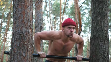 Strong and muscular man doing push ups on horizontal bar in forest. Hardy sportsman working out at nature. Athletic guy training outdoor. Concept of sport and active lifestyle. Close up Dolly shot Archivio Fotografico