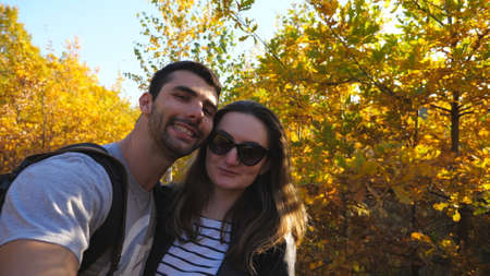 Portrait of happy smiling couple kisses while takes selfie photo with autumn garden at background. Young cheerful lovers stands at nature and looks into camera. Concept of loving. Slow motion Imagens - 154676689
