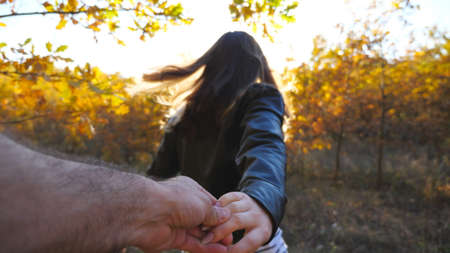 Follow me shot of young woman pulls her boyfriend along trail through small oak trees. Happy girl holds male hand and jogs along path in garden. Beautiful nature at background. Concept of loving. POV