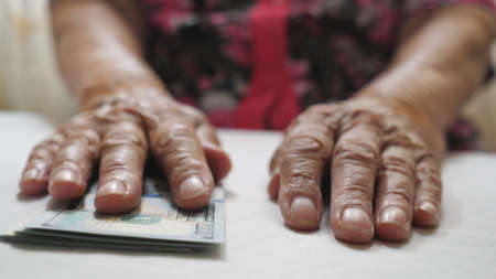 Elderly woman holds cash in arms and counts foreign currency over the table. Close up hands of old grandmother puts one hundred dollar banknotes on the desk. Money concept. Low view Slow motion