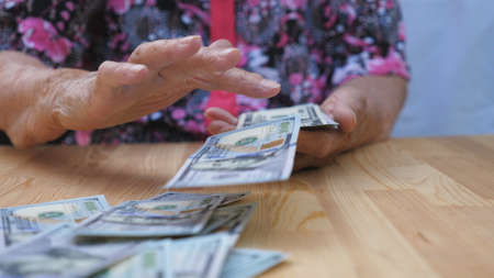 Dolly shot hands of elderly grandmother holds bundle of money and scatters foreign currency on the desk. Arms of old granny throws one hundred dollar bills on the table in front to camera. Slow motion Imagens