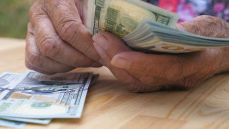 Low view of wrinkled female hands holds foreign currency and counts cash over the desk. Arms of old grandmother puts one hundred dollar banknotes on the table. Money concept. Slow motion