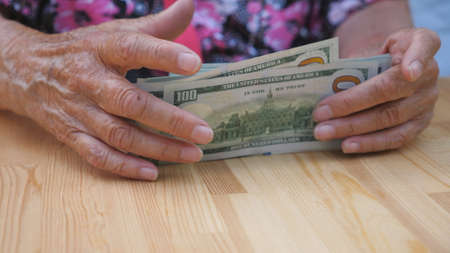 Wrinkled female hands takes out bills of foreign currency in pile from the desk. Arms of grandmother rakes a scattered one hundred dollar banknotes in bundle from the table. Low view Slow motion