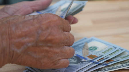 Close up of wrinkled female arms foreign currency and counts cash over the desk. Hands of elderly grandmother puts one hundred dollar banknotes on the table. Money concept. Slow motion Imagens