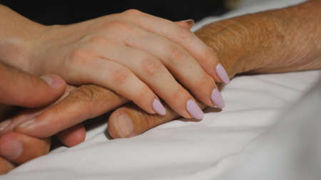 Granddaughter and grandson gently stroke hand of their grandma lying in bed hospital. Young woman and man comfort wrinkled arm of sick grandmother in medical clinic. Concept of care and love. Close up Imagens