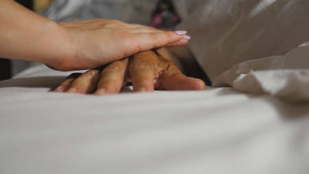 Girl takes and comforts hand of sick mature woman in medical clinic. Granddaughter gently touches wrinkled arm of her elderly grandmother lying in bed hospital. Daughter gives support to her parent