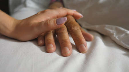 Granddaughter comforts wrinkled arm of sick mature grandma lying in bed hospital. Girl gently touches hand of her grandmother in medical clinic. Daughter shows care and love to her mother
