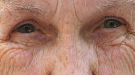 Close up of elderly grandma looks into camera with a sad sight. Portrait of senior grandmother strongly screws up her gray eyes. Facial expression of unhappy mature woman. Slow motion Imagens - 154259477