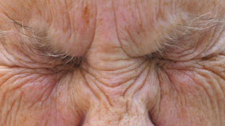 Portrait of mature woman strongly screws up her gray eyes and then open. Close up wrinkled face of elderly grandmother looks into camera with a surprised facial expression. Slow motion