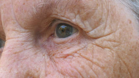 Portrait of half wrinkled female face looks into distance. Close up gray eye of mature woman stares and blinks with a disappointment sight. Facial expression of desperate and unhappy grandmother