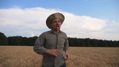 Young annoyed agronomist running to camera through the wheat field and trying to catch somebody. Angry farmer jogging among cereal meadow and tries to kick out someone from plantation. Front view Imagens - 154259486