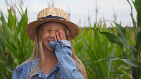 Small funny girl in straw hat looking into camera and laughs covering her face with hand on corn field. Portrait of happy little kid playing with her long blonde hair and straightening her straw hat. Imagens - 154242857