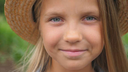 Portrait of happy small girl looking into camera and straightening her blonde hair and straw hat in the meadow. Close up of little smiling kid standing against the blurred background of corn field.