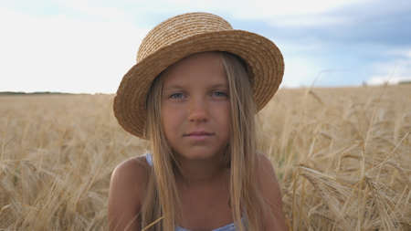 Portrait of little girl in straw hat looking into camera against the background of wheat field at organic farm. Beautiful small child with blonde hair sitting in the barley meadow. Close up