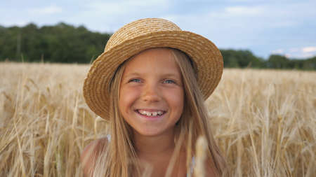 Portrait of beautiful little girl in straw hat looking into camera and laughs covering her face with hands. Happy small child sitting with joyful smile against the background of wheat field. Close up