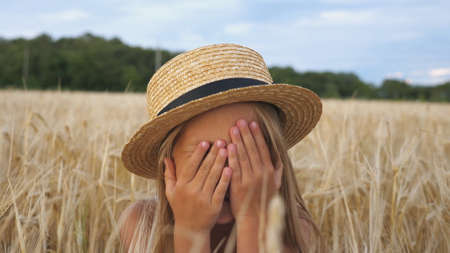 Portrait of beautiful little girl in straw hat looking into camera and laughs covering her face with hands. Happy small child sitting with joyful smile against the background of wheat field. Close up Imagens - 154259566