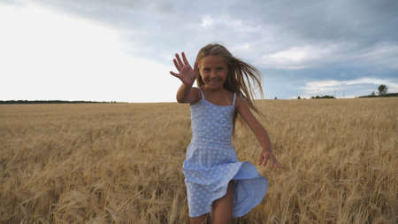 Close up of happy girl with long blonde hair running to the camera through barley field. Little smiling kid jogging over the wheat meadow. Cute child spending time at golden plantation. Slow motion Imagens - 154259579