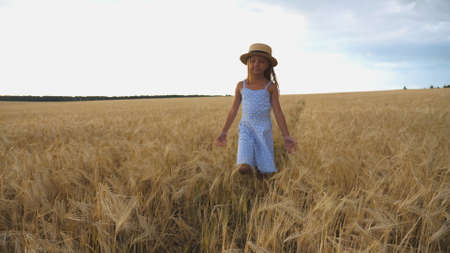 Close up of beautiful small girl with long blonde hair walking through wheat field. Cute child in straw hat touching golden ears of crop. Little kid in dress going over the meadow of barley Imagens - 154259640