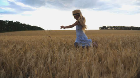 Beautiful girl with long blonde hair jogging over meadow of barley at overcast day. Cute happy child in straw hat running through wheat field. Small child having fun at golden plantation. Close up Imagens - 157499408