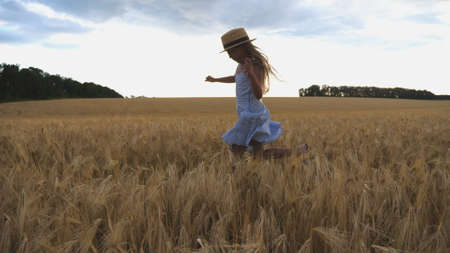 Beautiful girl with long blonde hair jogging over meadow of barley at overcast day. Cute happy child in straw hat running through wheat field. Small child having fun at golden plantation. Close up Imagens - 157499410