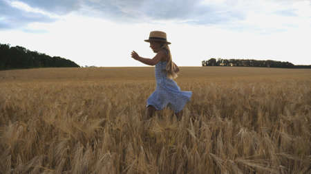 Beautiful girl with long blonde hair jogging over meadow of barley at overcast day. Cute happy child in straw hat running through wheat field. Small child having fun at golden plantation. Close up