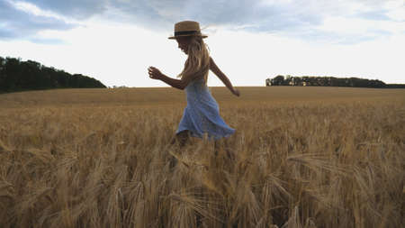 Beautiful girl with long blonde hair jogging over meadow of barley at overcast day. Cute happy child in straw hat running through wheat field. Small child having fun at golden plantation. Close up Imagens - 157499412
