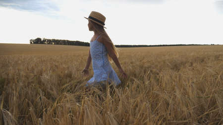 Close up of beautiful small girl with long blonde hair walking through wheat field. Cute child in straw hat touching golden ears of crop. Little kid in dress going over the meadow of barley Imagens - 157499416