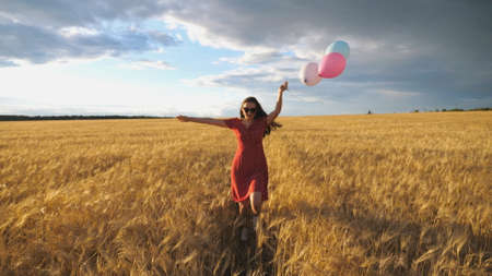 Young smiling woman with brown hair running through golden wheat field with balloons in hand. Beautiful happy girl in red dress having fun while jogging among barley plantation. Freedom concept Imagens - 157499425