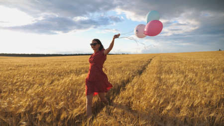 Young smiling woman with brown hair running through golden wheat field with balloons in hand. Beautiful happy girl in red dress having fun while jogging among barley plantation. Freedom concept
