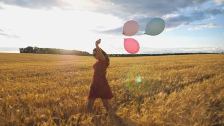 Young smiling woman with brown hair running through golden wheat field with balloons in hand. Beautiful happy girl in red dress having fun while jogging among barley plantation. Freedom concept Imagens - 157499428
