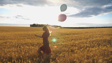 Young smiling woman with brown hair running through golden wheat field with balloons in hand. Beautiful happy girl in red dress having fun while jogging among barley plantation. Freedom concept Imagens - 157499429