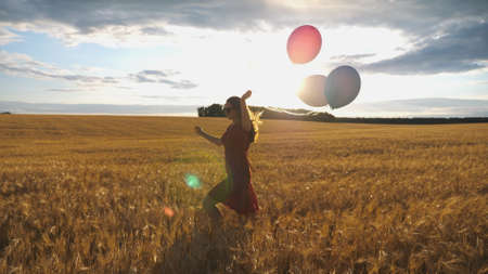 Young smiling woman with brown hair running through golden wheat field with balloons in hand. Beautiful happy girl in red dress having fun while jogging among barley plantation. Freedom concept Imagens - 157499430