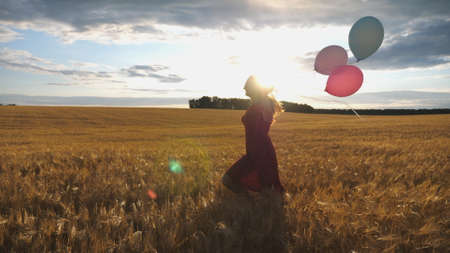 Young smiling woman with brown hair running through golden wheat field with balloons in hand. Beautiful happy girl in red dress having fun while jogging among barley plantation. Freedom concept Imagens - 157499431