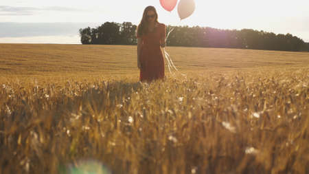 Young woman with brown hair walking through golden wheat field with balloons in hand. Beautiful girl in red dress going among barley plantation with sunlight at background. Freedom concept Imagens - 157499434