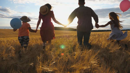 Happy family with two children holding hands of each other and running through wheat field at sunset. Young couple of parents with kids jogging among barley meadow and enjoying nature together. Imagens - 157499440