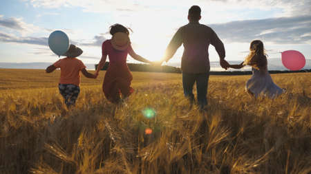 Happy family with two children holding hands of each other and running through wheat field at sunset. Young couple of parents with kids jogging among barley meadow and enjoying nature together. Imagens - 157499441
