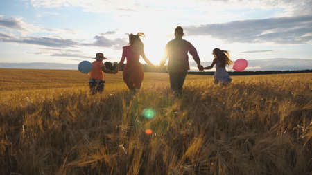 Happy family with two children holding hands of each other and running through wheat field at sunset. Young couple of parents with kids jogging among barley meadow and enjoying nature together. Imagens - 157499442