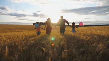 Happy family with two children holding hands of each other and running through wheat field at sunset. Young couple of parents with kids jogging among barley meadow and enjoying nature together.