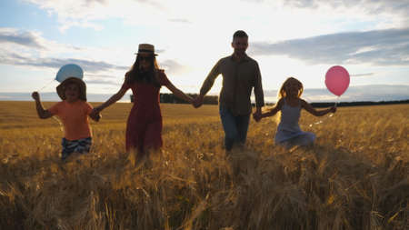 Young mother and father with kids holding hands of each other and jogging among barley meadow at sunset. Happy family with two children running through wheat field and enjoying nature together. Imagens - 157508599