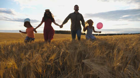 Young mother and father with kids holding hands of each other and jogging among barley meadow at sunset. Happy family with two children running through wheat field and enjoying nature together.