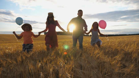 Young mother and father with kids holding hands of each other and jogging among barley meadow at sunset. Happy family with two children running through wheat field and enjoying nature together. Imagens - 157508601