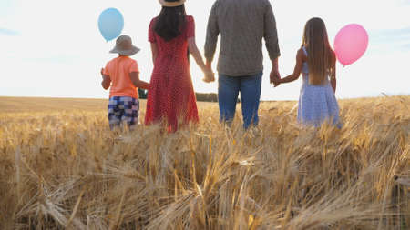 Young parents with kids holding hands of each other and standing on the barley meadow at sunset. Happy family with two children spending time together at wheat field and enjoying nature. Rear view Imagens - 157508603