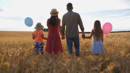 Young parents with kids holding hands of each other and standing on the barley meadow at sunset. Happy family with two children spending time together at wheat field and enjoying nature. Rear view Imagens - 157508604