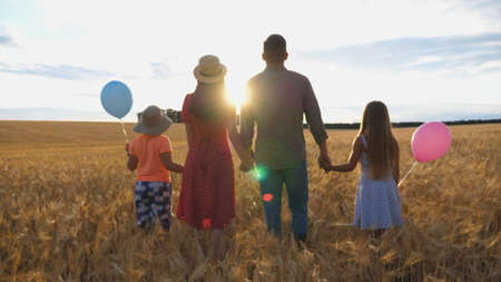 Young parents with kids holding hands of each other and standing on the barley meadow at sunset. Happy family with two children spending time together at wheat field and enjoying nature. Rear view Imagens - 157508606