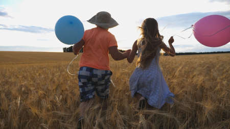 Small girl and boy holding hands of each other and running among barley plantation. Couple of little kids with balloons in arms jogging through wheat field at sunset. Concept of child love. Rear view Imagens - 157508607