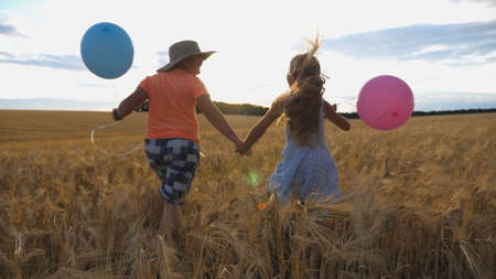 Small girl and boy holding hands of each other and running among barley plantation. Couple of little kids with balloons in arms jogging through wheat field at sunset. Concept of child love. Rear view