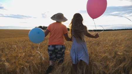 Small girl and boy holding hands of each other and running among barley plantation. Couple of little kids with balloons in arms jogging through wheat field at sunset. Concept of child love. Rear view Imagens - 157508610