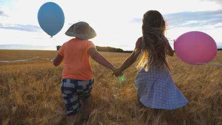 Small girl and boy holding hands of each other and running among barley plantation. Couple of little kids with balloons in arms jogging through wheat field at sunset. Concept of child love. Rear view Imagens - 157508611