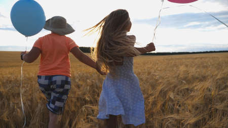 Small girl and boy holding hands of each other and running among barley plantation. Couple of little kids with balloons in arms jogging through wheat field at sunset. Concept of child love. Rear view Imagens - 157508613